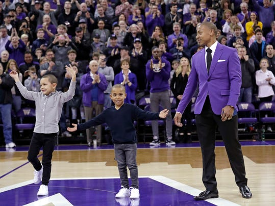 Former Washington guard Isaiah Thomas, right, looks on as his sons James, left, 7, and Jaiden, 6, encourage the crowd to cheer as Thomas is introduced during a ceremony retiring his jersey at halftime during an NCAA college basketball game against Colorado Saturday, Feb. 17, 2018, in Seattle. The Tacoma, Wash., native led the Huskies to three consecutive conference championships, and finished his three years with 1,721 career points, now eighth in all-time in scoring for men at the school. (AP Photo/Elaine Thompson)