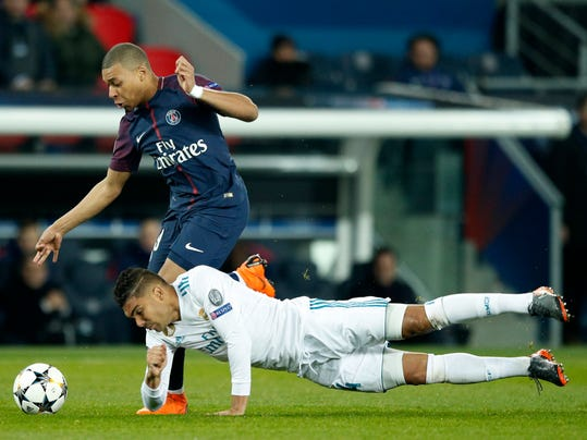 Real Madrid's Casemiro, bottom, tries to stop PSG's Kylian Mbappe during the round of 16, 2nd leg Champions League soccer match between Paris Saint-Germain and Real Madrid at the Parc des Princes Stadium in Paris, Tuesday, March 6, 2018. (AP Photo/Francois Mori)