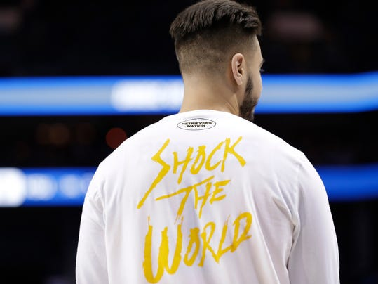 """A UMBC player wears a T-shirt with """"Shock The World"""" on it as the team warms up before their second-round game against Kansas State in the NCAA men's college basketball tournament in Charlotte, N.C., Sunday, March 18, 2018. (AP Photo/Gerry Broome)"""