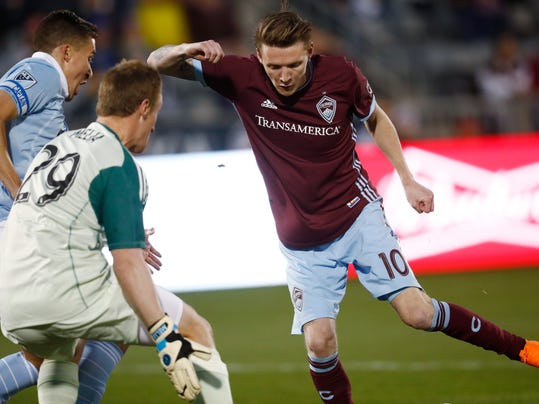 Colorado Rapids forward Joe Mason, right, scores a goal past Sporting Kansas City defender Matt Besler, back left, and goalkeeper Tim Melia in the first half of an MLS soccer match Saturday, March 24, 2018, in Commerce City, Colo. (AP Photo/David Zalubowski)