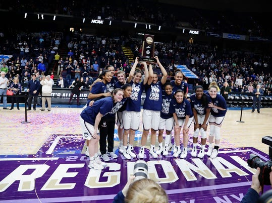 Connecticut players pose for photographs with the regional championship trophy as they celebrate following a women's NCAA college basketball tournament regional final game against South Carolina, Monday, March 26, 2018, in Albany, N.Y. (AP Photo/Frank Franklin II)