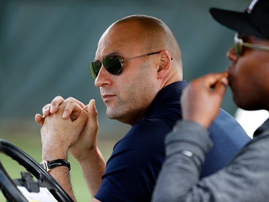 FILE - In this Feb. 14, 2018, file photo, Miami Marlins chief executive officer Derek Jeter watches spring training baseball practice from the shade of a golf cart, in Jupiter, Fla. The Jeter regime will debut when Miami right-hander Jose Urena makes his first opening day start against Cubs left-hander Jon Lester.(AP Photo/Jeff Roberson, File)