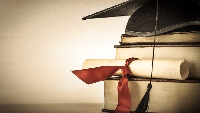 A mortarboard and graduation scroll, tied with red ribbon, on a stack of books.