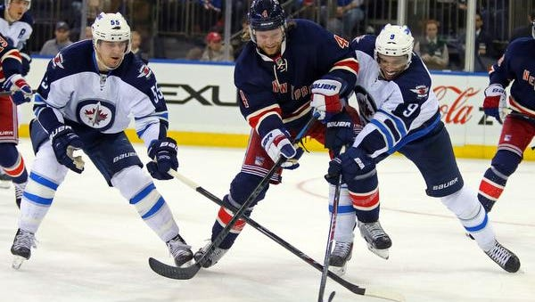 Rangers defenseman Mike Kostka battles for the puck with Winnipeg Jets forwards Evander Kane, right, and Mark Scheifele, left, during the third period at Madison Square Garden on Saturday night.