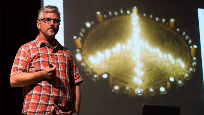 "Award-winning freelance photographer and author John Noltner spoke Tuesday at Lakeside Chautauqua's Hoover Auditorium. His multimedia exhibit, ""A Peace of My Mind,"" will be on display in Lakeside through Saturday."