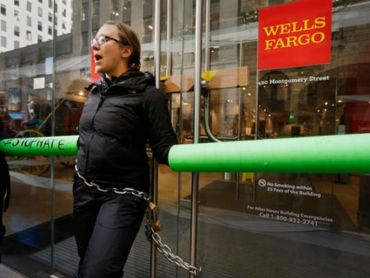 A protestor chained to the front door of Wells Fargo headquarters chants during an anti-Trump rally Friday, Jan. 20, 2017, in San Francisco. Protests against the inauguration of President Donald Trump are underway in California. Demonstrators gathered in the rain Friday at San Francisco's Civic Center Plaza and across the bay in Oakland at the Ronald Dellums Federal Building.