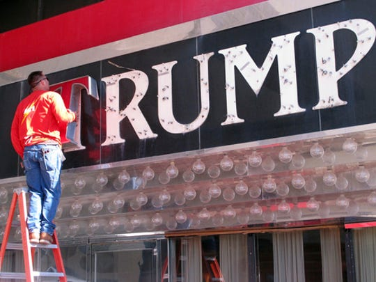FILE - In this file photo taken Oct. 6, 2014, a worker removes letters from a Trump logo in Atlantic City, N.J.China has granted preliminary approval for 38 new Trump trademarks, fueling concerns about conflicts of interest and preferential treatment of the U.S. president. The marks pave the way for branded spas, golf clubs, hotels, and even private body guard and escort services in China _though it's not clear if those businesses will actually materialize.