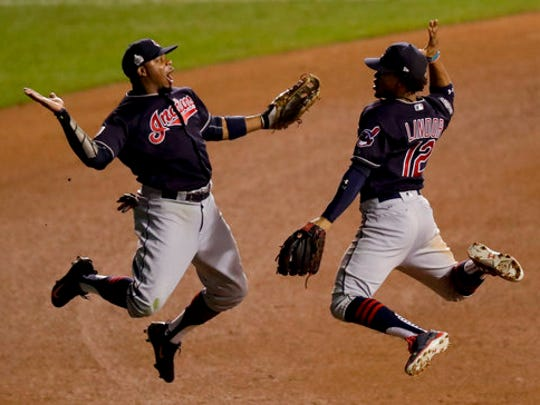 FILE - In this Oct. 29, 2016, file photo, Cleveland Indians left fielder Rajai Davis, left, and shortstop Francisco Lindor celebrate their win after Game 4 of the Major League Baseball World Series against the Chicago Cubs, in Chicago. Now that the Cubs have broken baseball's oldest curse, who's next? Maybe it's the Indians' turn.