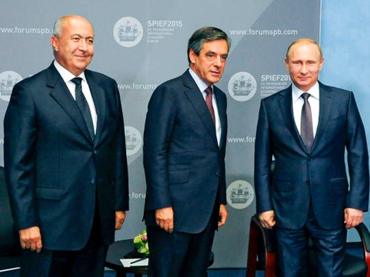 FILE - In this Wednesday, March 22, 2017 file photo, from right, Russian President Vladimir Putin, former French Prime Minister Francois Fillon and businessman Fouad Makhzoumi pose for photographers during their meeting on the sidelines of an economic forum in St. Petersburg, Russia. The Kremlin is dismissing a report that French presidential candidate Francois Fillon made 50,000 euros to set up a meeting between Russian President Vladimir Putin and a Lebanese oil magnate Fouad Makhzoumi at an economic forum in 2015.