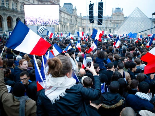 People wave French flags at the Louvre museum where