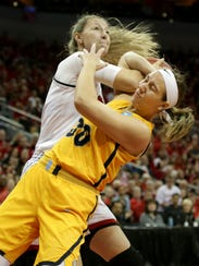 Louisville's Kylee Shook, left, is fouled by Marquette's