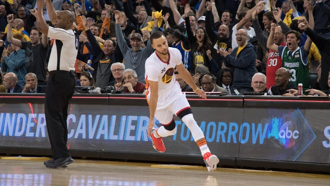 Golden State Warriors guard Stephen Curry (30) celebrates after making a half-court shot against the Los Angeles Clippers during the second quarter at Oracle Arena.