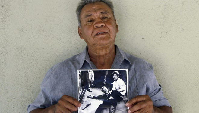 Juan Romero holding a Los Angeles Times photograph that shows Romero with Sen. Robert F. Kennedy at the Ambassador hotel in Los Angeles moments after Kennedy was shot.