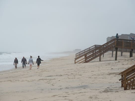 Beachgoers walk on the sand at Bethany Beach.