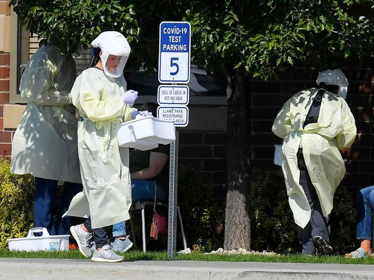 Workers test Utah State University students for COVID-19 on Sunday in Hyde Park, Utah. Students from four dorms were tested and quarantined after the virus was detected in the wastewater from those buildings.