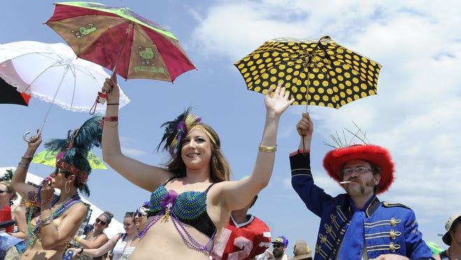 People dance during the kickoff parade at Bonnaroo on June 11, 2015.