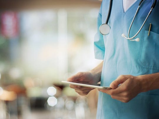 Medical professional holding a tablet.