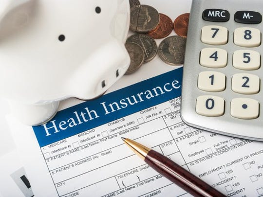 Health insurance form with piggy bank, change, and calculator