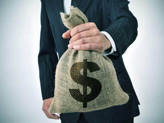 torso of man in suit holding out a stuffed burlap bag with a dollar sign on it