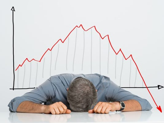 man-with-head-on-table-stock-chart-crash-in-background_large.jpg