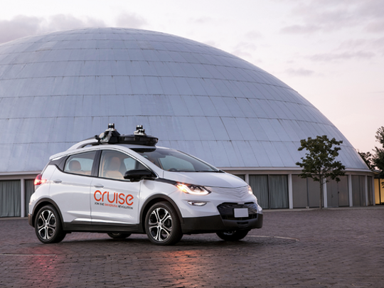 The GM Cruise AV, a small white hatchback with visible self-driving hardware.