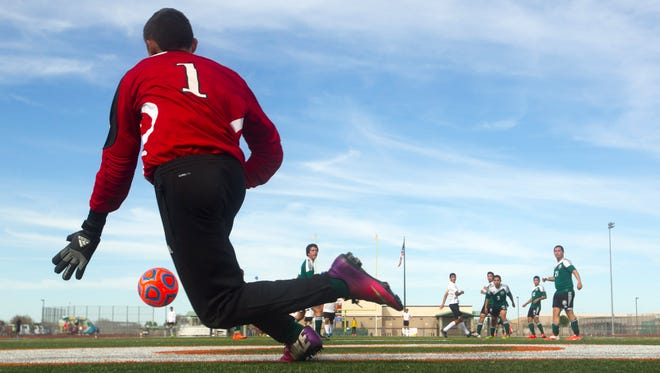 San Luis High goalie Romel Ojeda watches as a ball kicked by Queen Creek scores a goal during the second  half of the Division II boys soccer final at Campo Verde High School in Gilbert on Saturday, February 14, 2015.
