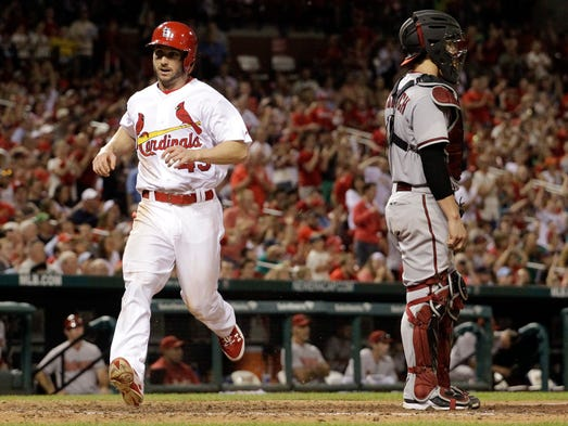The Cardinals' Shane Robinson, left, scores on a single by Matt Carpenter as Diamondbacks catcher Tuffy Gosewisch stands by during the eighth inning Thursday, May 22, 2014, in St. Louis.