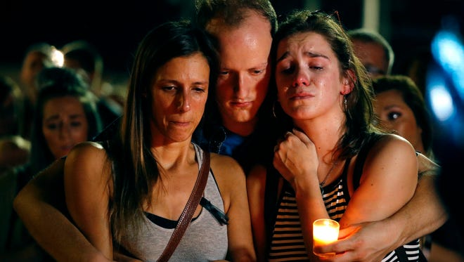 Mallory Cunningham, left, Santino Tomasetti, center, and Aubrey Reece attend a candlelight vigil in the parking lot of Ride the Ducks Friday, July 20, 2018, in Branson, Mo. One of the company's duck boats capsized Thursday night resulting in over a dozen deaths on Table Rock Lake.