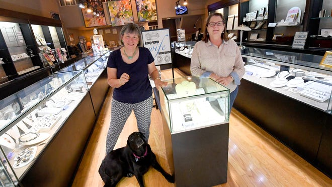 Co-owners Dana Flanders and Becky Corns stand within their business, Crown Jewelers, with Stella in downtown Staunton on Friday, August 3, 2018. The pair have recently sold the business.