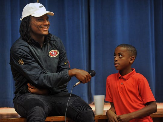 Adrian Colbert, left, grins after asking Booker T. Washington Elementary 5th grader De'irre Sumpter what he wanted to do when he grows up. Colbert was recently drafted into the NFL to play for the San Francisco 49ers. Sumpter said he, too, would like to play professional football, but for the Dallas Cowboys.