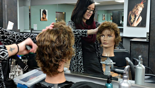"Ebony Castillo cuts the hair of a mannequin head, ""Candy,""  at Hair Dynamics on December 29, 2015."