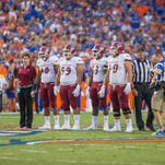 Lori Paulson holds the hand of a New Mexico State University football player  during the coin flip at this year's game at the University of Florida.