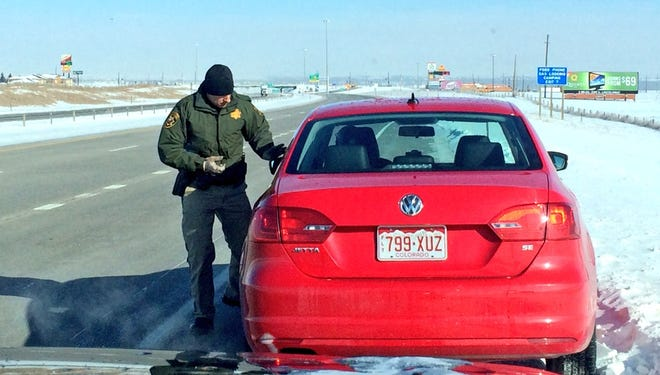 Bundled up against the minus-22-degree temperature, Wyoming state trooper Karl Germain issues a warning to a Colorado driver who was speeding across the state line on Interstate 25 in late February.