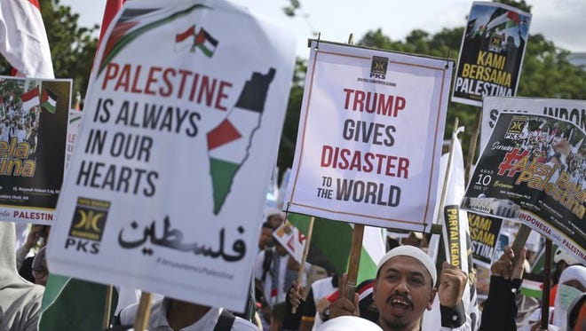 Muslims hold posters during a rally against President Donald Trump's decision to recognize Jerusalem as Israel's capital outside the U.S. Embassy in Jakarta, Indonesia, on Dec. 10, 2017. Hundreds of people across the most populous Muslim country staged protests Friday against Trump administration's policy shift on the contested city.