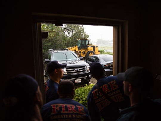 Fire fighters look out of the door at the storm at