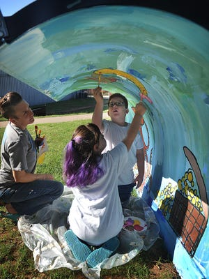 Kane Hoover, 7, and Emily Akin, 7, paint an underwater scene on a snow plow blade with the help of teaching artist Amber Scott.