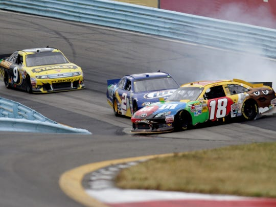 Kyle Busch spins out during a last-lap incident in front of Brad Keselowski and Marcos Ambrose at the Finger Lakes 355 at The Glen at Watkins Glen in 2012. Ambrose held off Keselowski to win that year.