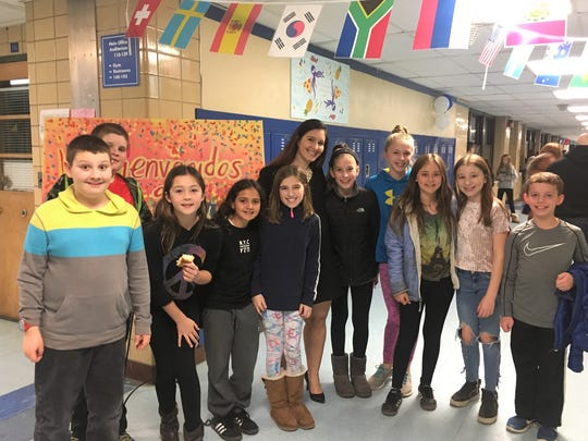 Left to right: Wilson School 5th graders Benjamin Wancier, Brenton Hatch, Gillian Kayut, Abigail Autmezguine, Keri Rothenberg, Kate Fischer, Caterina Carayannopoulos, Tatum Rosen, Elizabeth Verga, and Carson Donnelly join elementary Spanish teacher Lisa DeSousa (center) at Café Cultural on March 28.