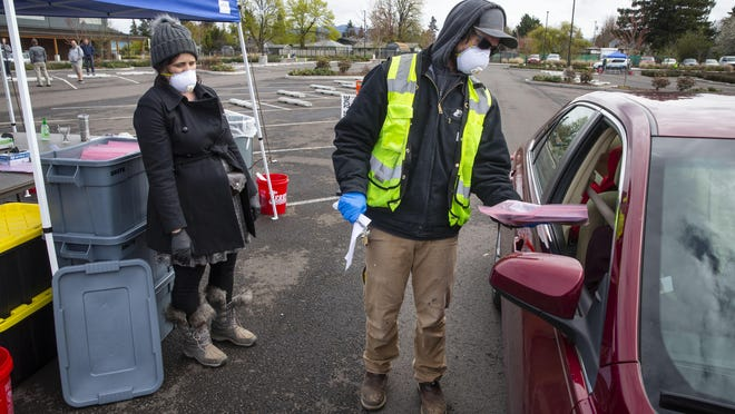 Ame Beard principal at The Academy of Arts and Academics, left, and maintenance department worker Ryan Webb hand out laptops to students and their parents in the parking lot of Hamilin Middle School in Springfield in April. [Chris Pietsch/The Register-Guard file] - registerguard.com