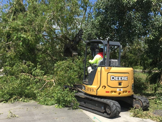 Crews that had been working on road construction on McGregor Boulevard in Fort Myers use heavy equipment to break down fallen trees on Tuesday, Sept. 12.