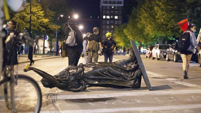 """Wisconsin's """"Forward"""" statue lies in the street on Capitol Square in Madison, Wis. Tuesday, June 23, 2020. Protesters tore down the statue, another of Union Civil War Col. Hans Christian Heg, assaulted a state senator and set a small fire in a city building downtown after the arrest of a Black activist earlier in the day."""