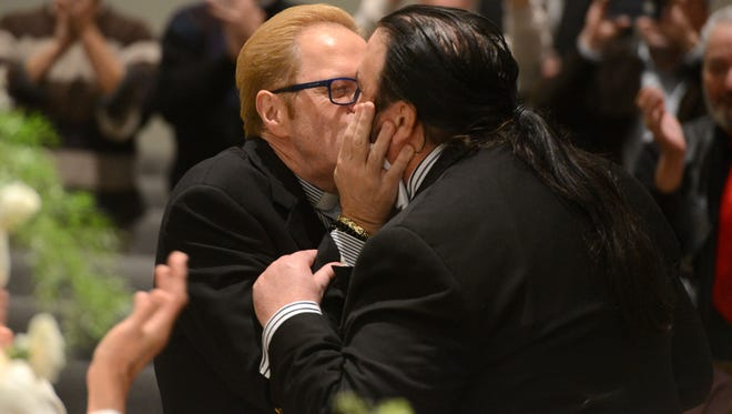 Rev. Jim Merritt, left, and Al Leach, kiss after being married by Rev. Lee Carlton, center, on Tuesday at the Holy Cross Metropolitan Community Church on the first day of legal same-sex marriage in Florida. Leach and Merritt were excited to finally tie the knot legally after being together for over 20 years.
