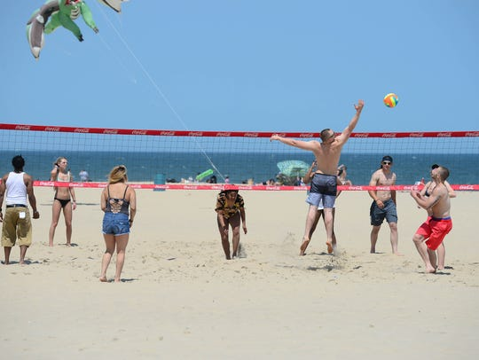 A group of people play some beach volleyball before