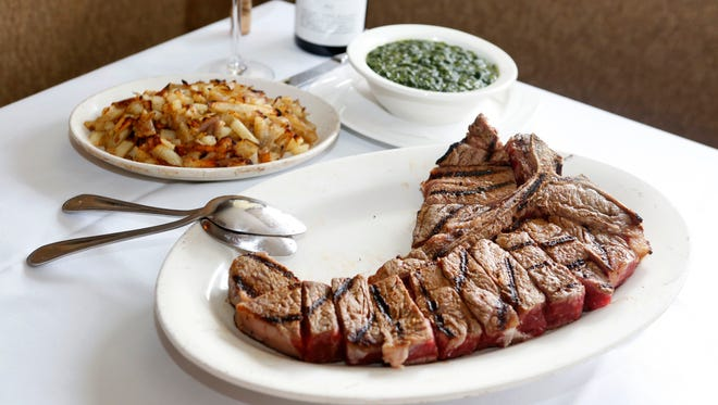 The dry-aged prime porterhouse, with creamed spinach and German fries, is photographed at Sparkill Steakhouse March 20, 2014.