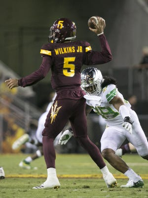 ASU quarterback Manny Wilkins passes as Oregon Kaulana Apelu (39) goes in for the tackle during the second quarter of PAC-12 college football game at Sun Devil Stadium in Tempe on Saturday, September 23, 2017.