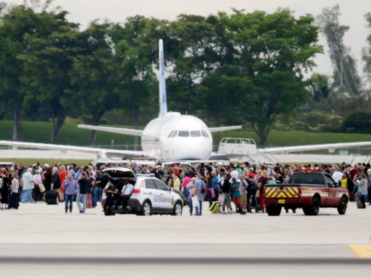 People stand on the tarmac at the Fort Lauderdale-Hollywood International Airport after a shooter opened fire inside a terminal of the airport, killing at least five and wounding others before being taken into custody, Friday, in Fort Lauderdale, Fla.
