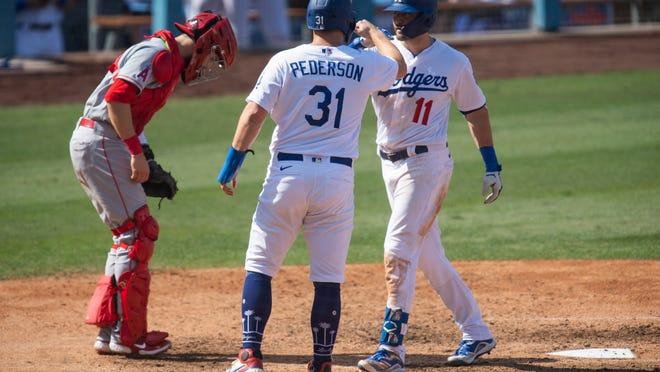 Los Angeles Dodgers' A.J. Pollock, right, celebrates his two-run home run with Joc Pederson, center, during the seventh inning of a baseball game against the Los Angeles Angels in Los Angeles, Sunday, Sept. 27, 2020. (AP Photo/Kyusung Gong)