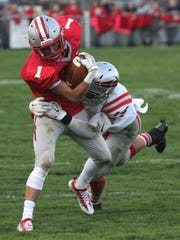 Shelby's Brady Hill is tackled by Bellevue's Hunter Martin during Friday's game at Skiles Field.