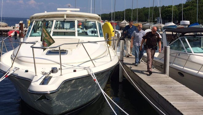 Door County Sheriff's Deputy Robert Sitte and investigators Jon Gilson and Chris Neuville photographed the boat owned by missing Dr. Jeffrey Whiteside at the Ephraim Yacht Harbor Marina on Friday.