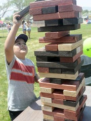 Junior Luna-Zarate stacks a block on a giant game of
